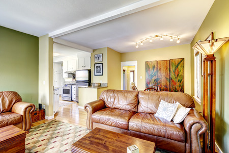 Home interior in yellow and green colors with brown leather couch and chair photo