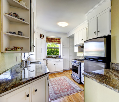 refrigerator kitchen: Kitchen area with white cabinets, granite tops and steel refrigerator