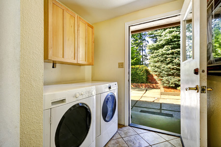 dryer  estate: Simple laundry room with white appliances in old house with exit to backayrd