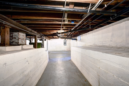 basement: Empty basement in old house with white walls and concrete floor