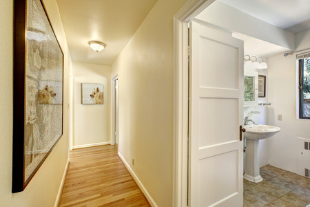 bathroom design: Narrow hallway with hardwood floor and ivory walls. Exit to bahtroom