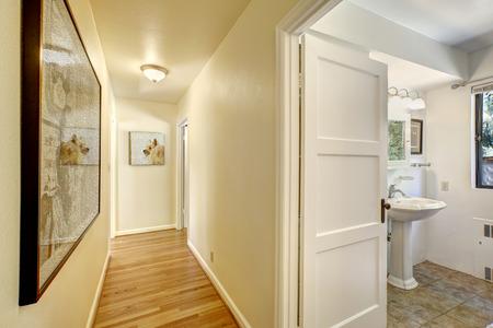 bathroom wall: Narrow hallway with hardwood floor and ivory walls. Exit to bahtroom