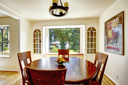 round chairs: Bright dining are with window and built-in cabinets . Wooden round dining table with chairs Stock Photo