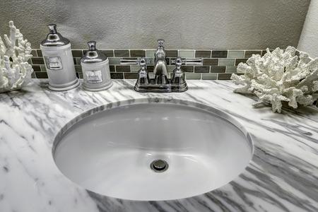Modern bathroom vanity cabinet with white granite top. Sink view. White sink with steel faucet and decorated corals Foto de archivo