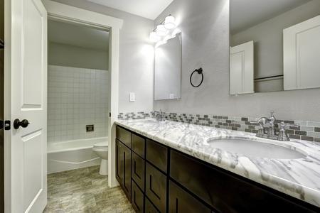 brown granite: Bathroom vanity cabinet with white granite top and mirrors
