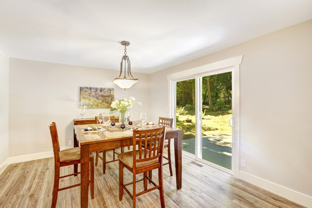 Bright ivory dining room with walkout patio. Wooden dining table with chairs