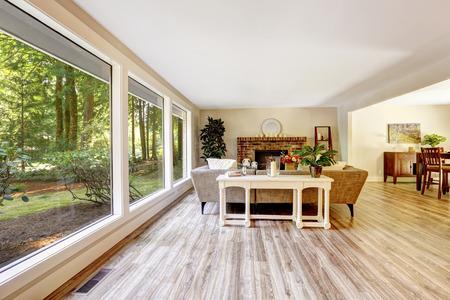 れんが造りの暖炉、ソファ、白のテーブルとガラスの壁に広々 とした明るいリビング ルーム