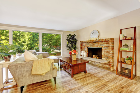 fireplace living room: Spacious bright living room with brick fireplace, couch, wooden coffee table and glass wall