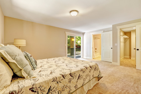 Spacious master bedroom interior in creamy tones with walkout deck, closet and bathroom photo