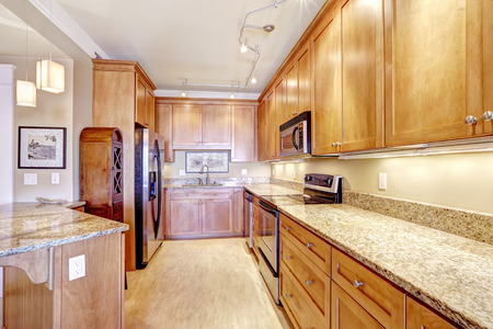 kitchen cabinets: Spacious kitchen room with wooden storage cabinets, granite tops, steel appliances and island