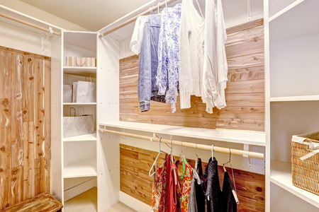 Walk-in closet with solid wood planks and white storage shelves Stock Photo