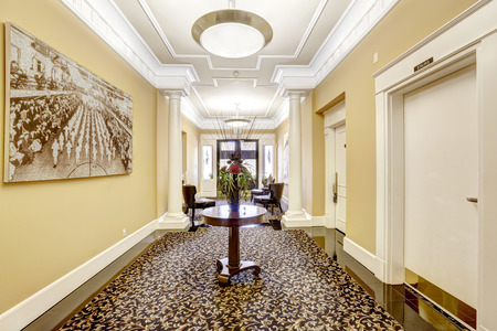 rug: Long hallway with black tile floor and rug on it decorated eith round table an flowers. Residential building in Tacoma, WA Stock Photo