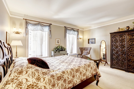 antique chair: Bedroom with beautiful carved wood bed , wardrobe and antique chair with mirror Stock Photo