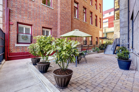 tacoma: Old brick building with courtyard. Courtyard with brick tile floor decorated with decorative trees