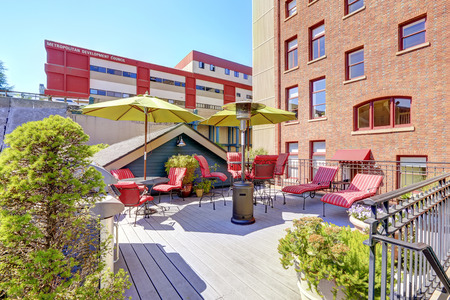 tacoma: Old brick building with deck for its residents. Deck with red chars, umbrella and barbecue