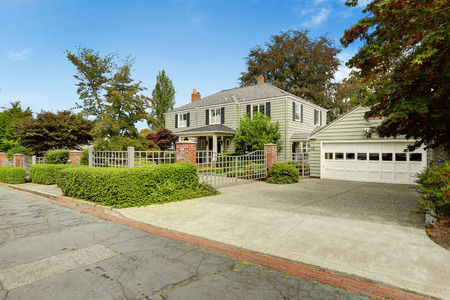 real estate house: Luxury real estate in Tacoma, WA. House with big garage and driveway. Fence with brick columns