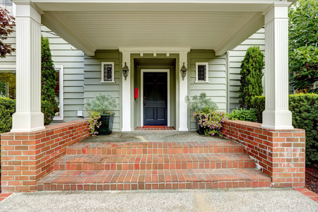 Spacious entrance porch with columns and brick tirm. Porch decorated with flower pots photo