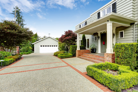 appeal: Luxury real estate in Tacoma, WA. Entrance porch with columns and brick tirm, beautiful curb appeal and garage with driveway Stock Photo