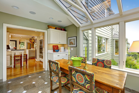 sunroom: Sunroom patio area with transparent vaulted ceiling, wooden dining table with colorful chairs