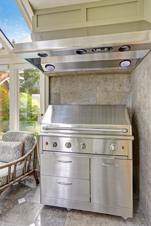 sunroom: Steel new barbecue with hood. Grey tile wall trim in screened patio area