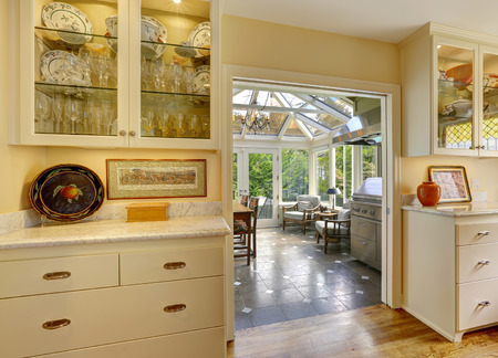 sunroom: Kitchen room with exit to patio area in sunroom. Kitchen cabinets with glass doors and white granite tops