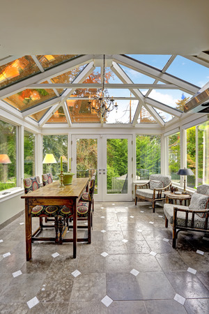 sunroom: Sunroom patio area with transparent vaulted ceiling, Dining table set with sitting area