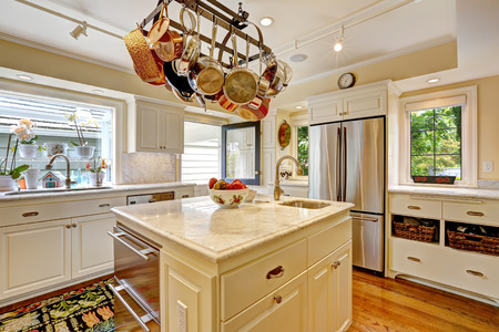 kitchen island: White kitchen with white granite tops, island and hanging pot rack