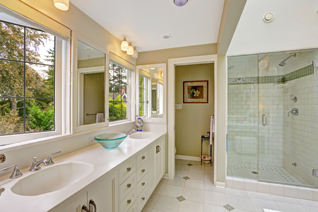 Spacious bright bathroom with white storage combination and glass door shower