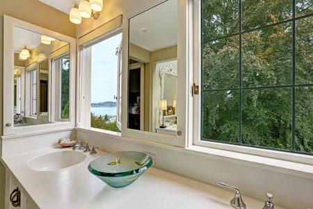bathroom mirror: White bathroom vanity cabinet with white counter top, cabinets with mirror and window with bay view Stock Photo
