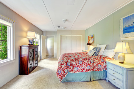 Bright simple bedroom interior with colorful bedding, old nightstand and wooden cabinet Stok Fotoğraf