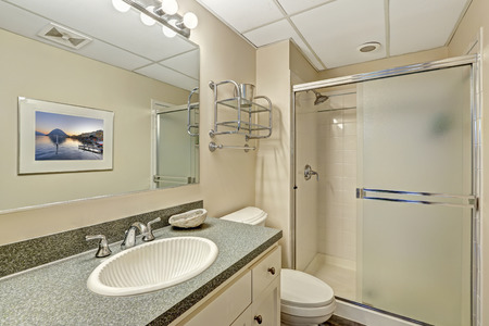 bathroom interior: Bathroom vanity cabinet with granite top and desinged sink and shower with slide glass door