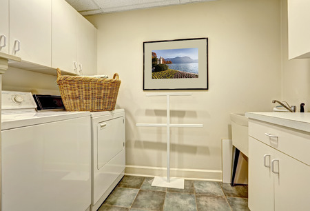 Simple light tones laundry room wtih white cabinet and old appliances Stock Photo