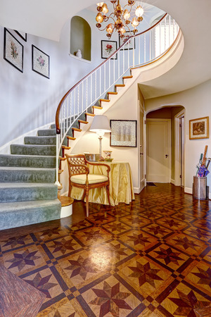 foyer: Beautiful spiral staircase with railings and carpet steps in luxury foyer with high ceiling and designed hardwood floor