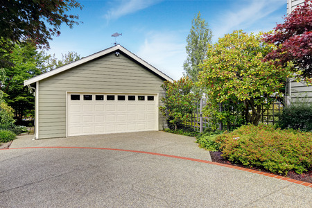 concrete: Garage with concrete driveway with trees alongside