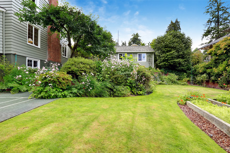 American house with big beautiful garden. Lawn and blooming bushes photo