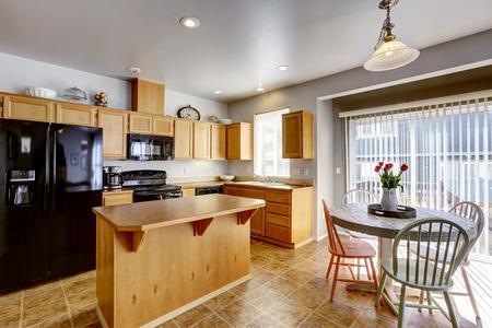 black appliances: Tavolo da pranzo rustico con tulipani in camera cucina con isola e nero elettrodomestici