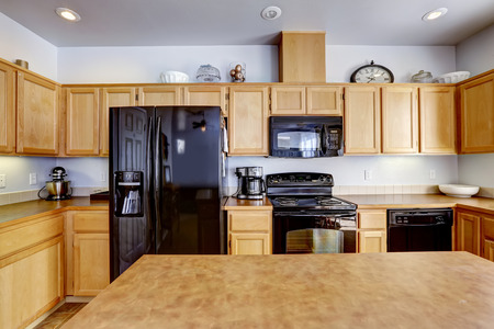 counter top: Light brown kitchen room with island and black appliances