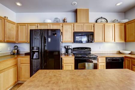 black appliances: Luce marrone sala cucina con isola e nero elettrodomestici