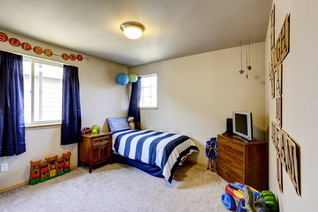 bedroom design: Decorated boys room interior with blue curtains, and stripped blue bedding Stock Photo