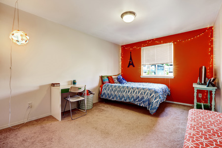 Bedroom interior with bright red wall. Furnished with a single bed, desk and table with tv photo