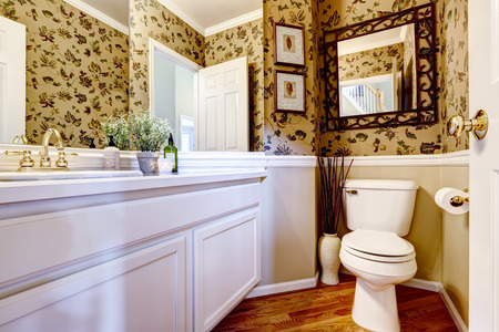 white trim: Beautiful restroom with large mirror and wallpaper wall trim. Bright white cabinet with gold color faucet Stock Photo
