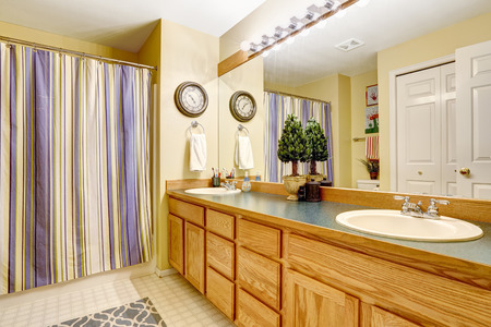 stripped: Bathroom interior with bathroom vanity cabinet with large mirror and stripped purple curtain