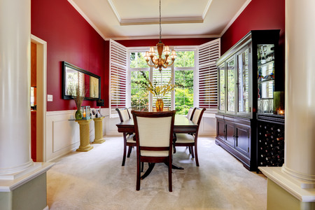 dining table and chairs: Luxury dining room with bright red wall and white french window.