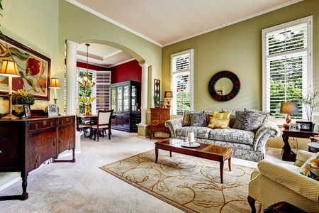 family sofa: Luxury house interior. Light green family room with antique cabinets and sofa