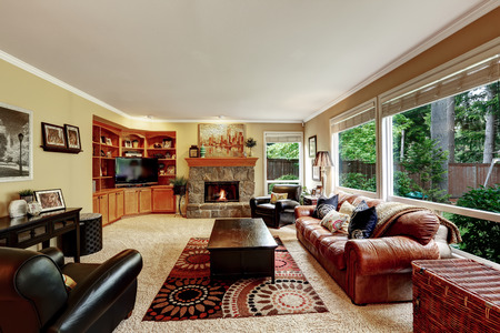Luxury family room with cozy stone trimmed fireplace. Rich leather couch and armchair create comfort atmosphere photo