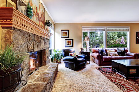 Luxury family room with cozy stone trimmed fireplace. Rich leather couch and armchair create comfort atmosphere