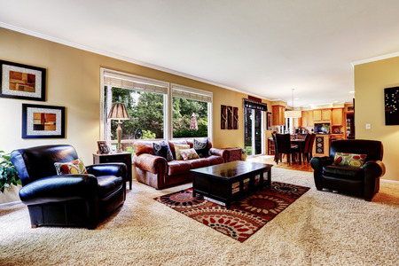 dining room: Luxury family room with rich leather couch and armchair .