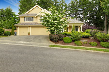 two car garage: House exterior with two car garage and driveway. Beautiful landscape