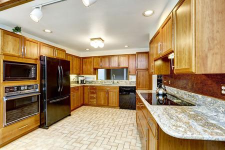 black appliances: Bella brillante cucina interna. Combinazione di mobili in legno con ripiani in granito ed elettrodomestici neri