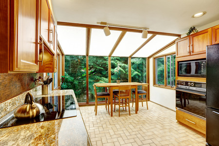 vaulted ceiling: Beautiful bright kitchen interior. Dining area with transparant glass wall and vaulted ceiling